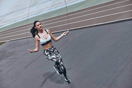 Pushing hard to win. Top view of beautiful young woman in sports clothing skipping rope while exercising outdoors Stock fotó