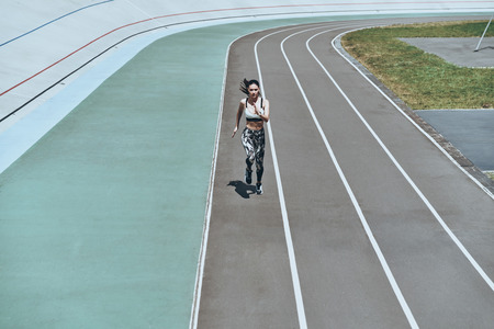 Everything is possible. Full length top view of young woman in sports clothing running while exercising outdoors