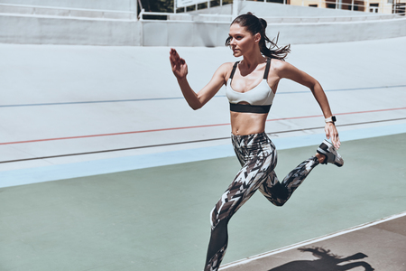 Everything is possible. Beautiful young woman in sports clothing running while exercising outdoors