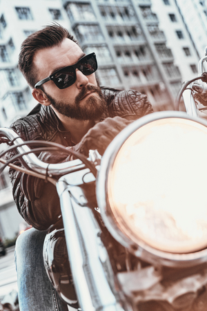 Real macho. Handsome young man in leather jacket and sunglasses riding motorbike while spending time outdoors