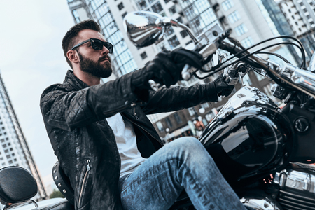 Heartbreaker. Handsome young man in leather jacket and sunglasses riding motorbike while spending time outdoors