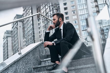 What if... Good looking young man in full suit holding disposable cup and looking away while sitting on the stairs outdoors