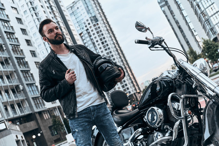 Do you want to take a ride? Handsome young man in leather jacket looking away while standing near the motorbike outdoors Stock Photo