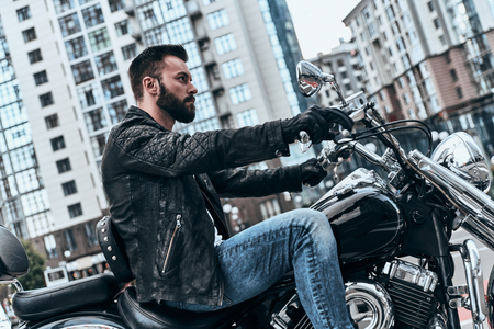 Just him and the road. Handsome young man sitting on the motorbike while spending time outdoors