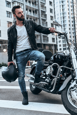 In love with motorcycle. Full length of handsome young man in leather jacket looking away while standing near the motorbike outdoors Stock Photo