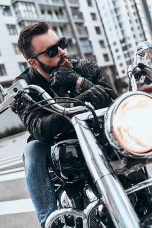 Looking great. Handsome young man in leather jacket and sunglasses riding motorbike while spending time outdoors