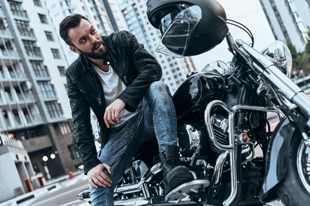 Enjoying his lifestyle. Handsome young man in leather jacket looking away while sitting on the motorbike outdoors