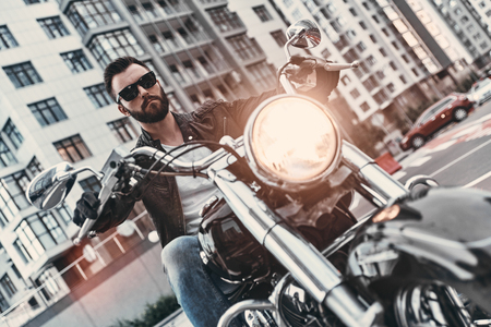 Dangerous. Handsome young man in leather jacket and sunglasses riding motorbike while spending time outdoors