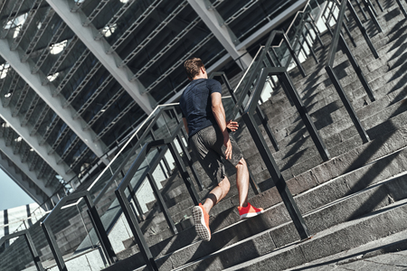 Ready to overcome any obstacle. Full length of young man in sports clothing running up the stairs while exercising outside