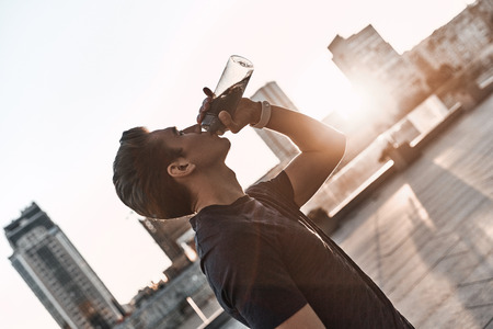 Hydrating. Young man in sports clothing drinking water while standing outside