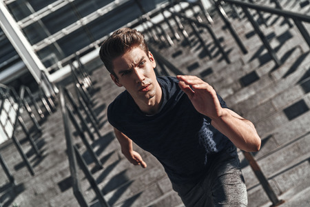 His best speed. Top view of young man in sports clothing running on the stairs while exercising outside