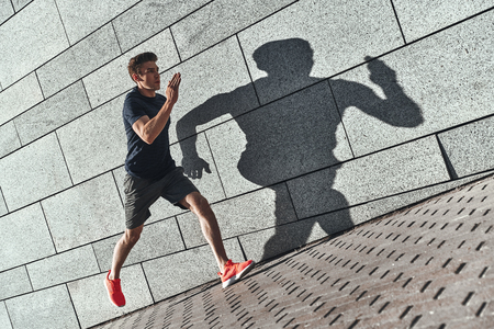 Sport is the way of life. Full length of young man in sports clothing running while exercising outside