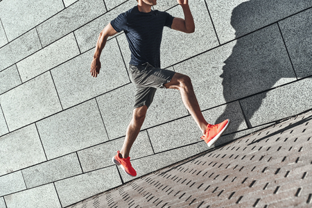 Full of energy. Close up of young man in sports clothing running while exercising outside