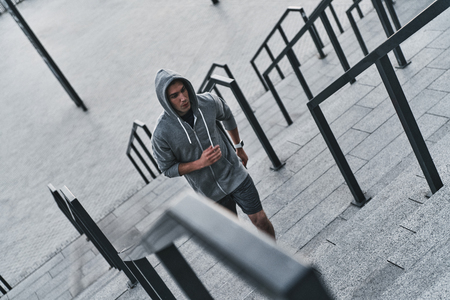 Never give up. Top view of young man in sports clothing exercising while standing on the stairs outdoors 스톡 콘텐츠