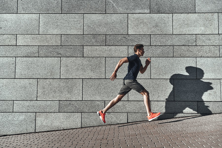 Morning workout. Full length of young man in sports clothing running while exercising outside