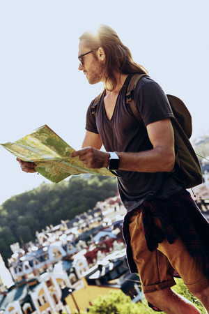 Freedom. Handsome young man in casual clothing holding map and looking away while standing on the hill outdoors