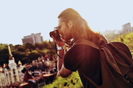 Nice shot. Young man in casual clothing photographing the view while standing on the hill outdoors
