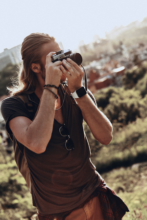 His passion. Young man in casual clothing photographing the view while standing on the hill outdoors