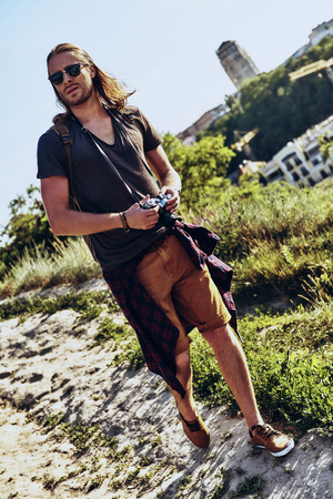 Searching for new direction. Full length of young man in casual clothing going somewhere while walking on the hill outdoors Stock Photo