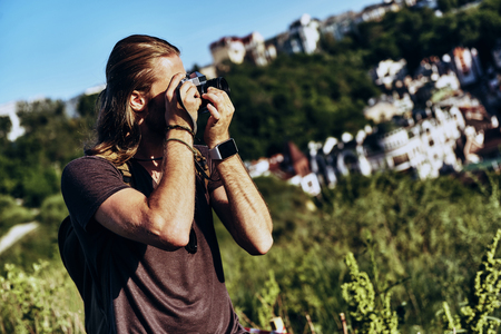 Great shot. Young man in casual clothing photographing the view while standing on the hill outdoors
