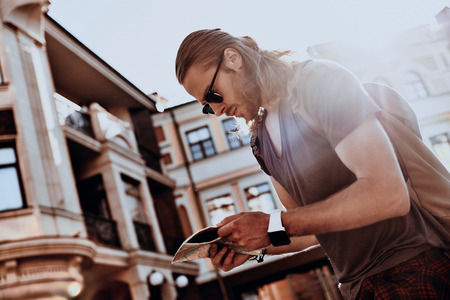 Where is it? Handsome young man in casual clothing looking at map while walking outdoors