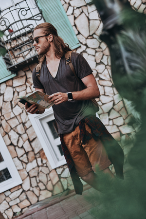 Modern tourist. Handsome young man in casual clothing holding map and looking away while standing outdoors