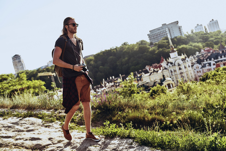 Beautiful places. Full length of young man in casual clothing going somewhere while walking on the hill outdoors