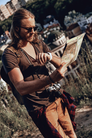 Timing. Handsome young man in casual clothing holding map and checking the time while standing on the hill outdoors