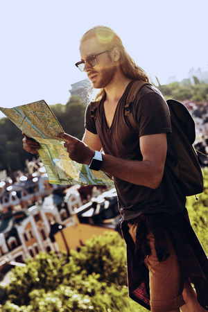 Where to go next? Handsome young man in casual clothing looking at map while standing on the hill outdoors