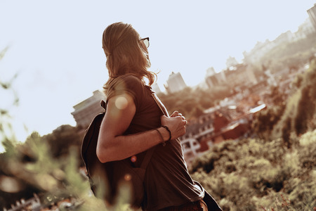 Amazed by the beauty. Young man in casual clothing looking at view while standing on the hill outdoors