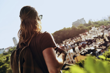 What a view! Handsome young man in casual clothing looking at view while standing on the hill outdoors