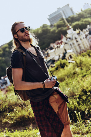 Enjoying the travel. Handsome young man in casual clothing looking away while standing on the hill outdoors