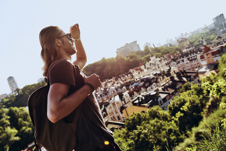 Perfect view. Handsome young man in casual clothing looking at view while standing on the hill outdoors Stock Photo