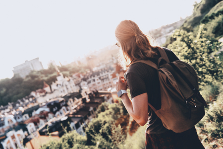 Young and free. Rear view of young man in casual clothing looking at view while standing on the hill outdoors Imagens
