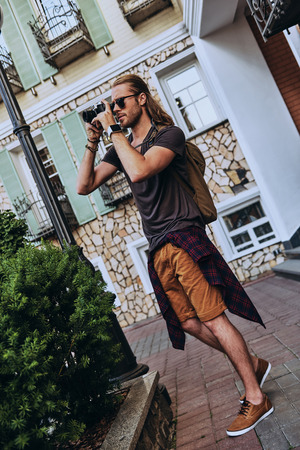 Capturing the moment. Full length of handsome young man in casual clothing photographing something while standing outdoors Stock Photo