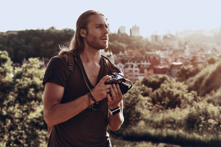 Looking for perfect composition. Young man in casual clothing photographing the view while standing on the hill outdoors