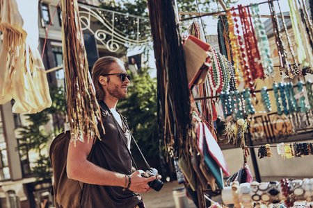 Souvenirs. Handsome young man in casual clothing standing near the market stall while spending time outdoors