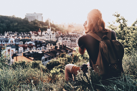 Beautiful view. Rear view of young man in casual clothing photographing the view while sitting on the hill outdoors