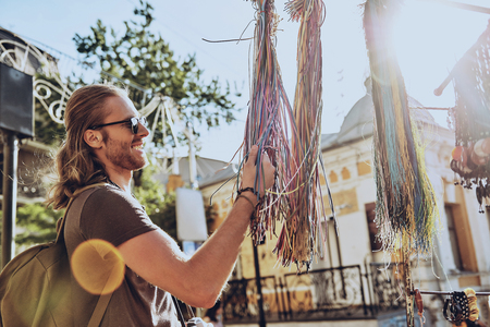 What a beauty! Handsome young man in casual clothing choosing necklace and smiling while standing near the market stall outdoors Stock Photo