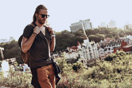 Right place to think. Handsome young man in casual clothing walking on the hill outdoors while enjoying his travel Stock Photo