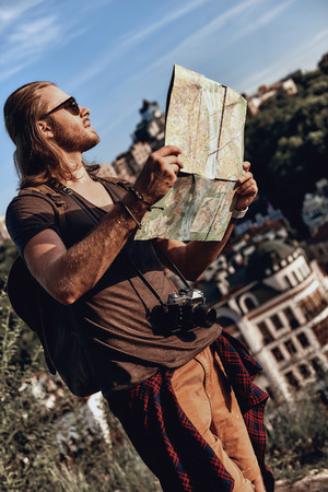 In the right place. Handsome young man in casual clothing holding map and looking away while standing on the hill outdoors Stock Photo