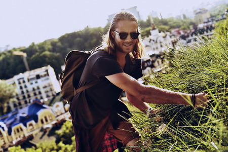 Real explorer. Handsome young man in casual clothing looking at camera and smiling while standing on the hill with buildings in the background Stock Photo