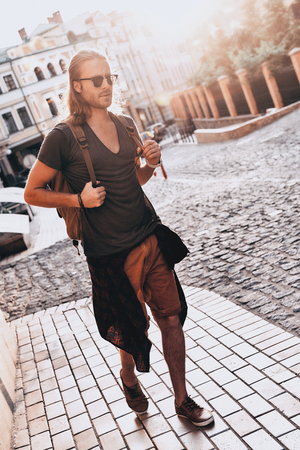 Summer trip. Full length of young man in casual clothing wandering empty street while walking outdoors Фото со стока