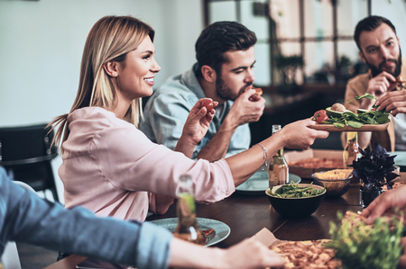 Great evening with friends. Group of young people in casual clothing eating and smiling while having a dinner party indoors Stock Photo