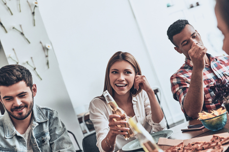 Good time with friends. Beautiful young people in casual wear talking and smiling while having a dinner party indoors Stock Photo