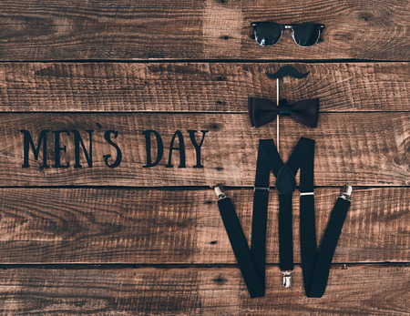 Mens day. High angle shot of suspenders, prop, bow tie and eyewear lying on wooden desk Stock Photo
