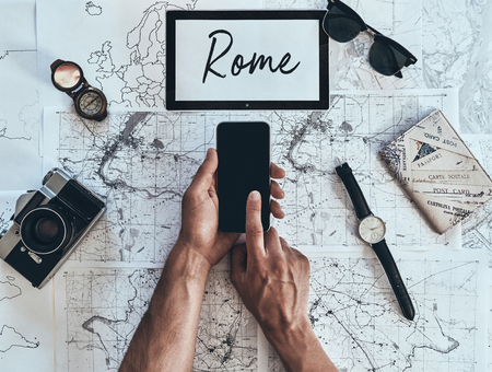 Rome. Close up top view of man using smart phone with sunglasses, photo camera, compass, watch and passport lying on map around
