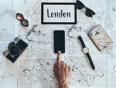 London is new destination. Close up top view of man using smart phone with sunglasses, photo camera, compass, watch and passport lying on map around Stock Photo