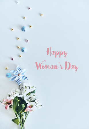 Happy women's day! High angle shot of flowers lying against white background 写真素材 - 105579645