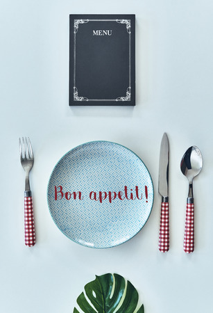 Food concept. High angle shot of empty plate, fork, spoon, knife closed menu lying against white background